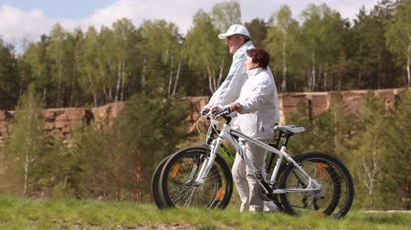 cycle : Senior couple walking with bicycles by the pit Stock Footage