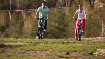 relação : Two young people cycling by the pit Stock Footage