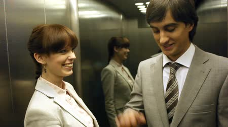 asansör : Two colleagues entering the lift and having fun inside