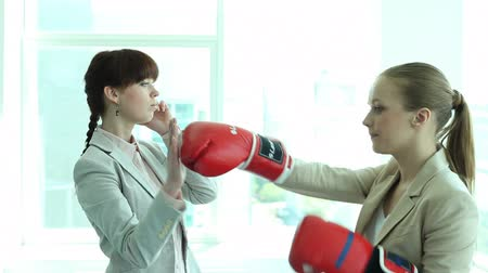 puncs : A businesswoman talking on the phone and her colleague boxing her Stock mozgókép