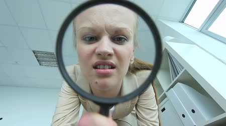 zvětšit : Pretty woman looking through spy glass in office