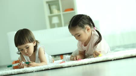 Пол : Two little sisters sitting on floor and drawing with highlighters