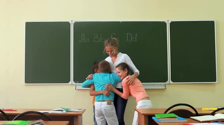 učitel : Three pupils coming up to their teacher and embracing her Dostupné videozáznamy