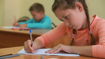 alapfokú : Little girl sitting at desk in school and writing Stock mozgókép