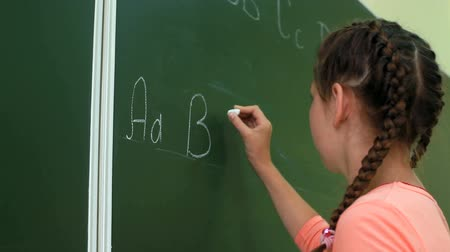 lousa : Little girl writing ABC on blackboard