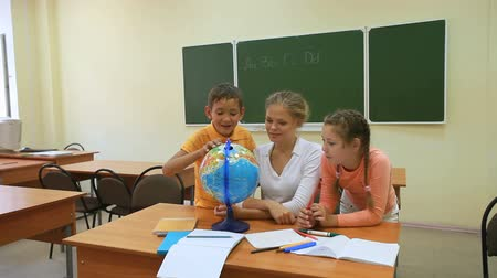 öğretim : Two pupils and their teacher looking at globe in classroom Stok Video