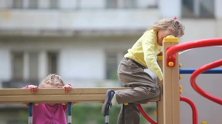 outside : Two little girls amusing on playground net Stock Footage