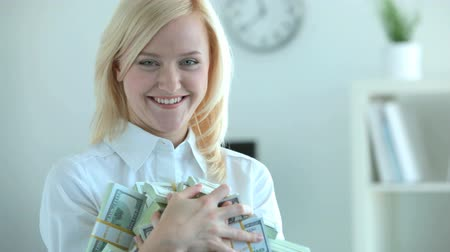 bogaty : Happy blonde holding heap of dollar bills in her hands