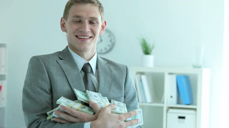 boldogság : Businessman holding a heap of dollar bills in office Stock mozgókép