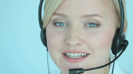 fejhallgató : Customer support representative consulting clients online and smiling at camera Stock mozgókép