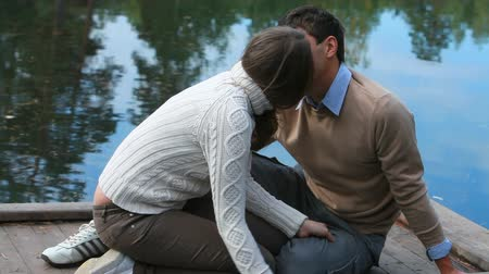 romantic couple : Young couple sitting on pier and kissing