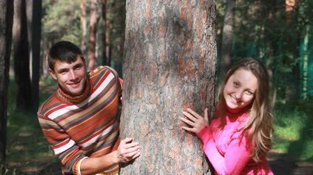 társkereső : Young couple hiding behind tree trunk, looking at camera and smiling