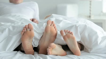 romantic couple : Feet of playful couple on bed stuck out of blanket
