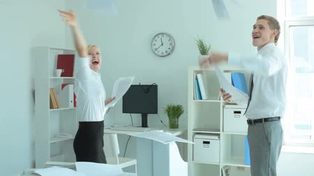 скрепки : Two joyful colleagues throwing papers in office
