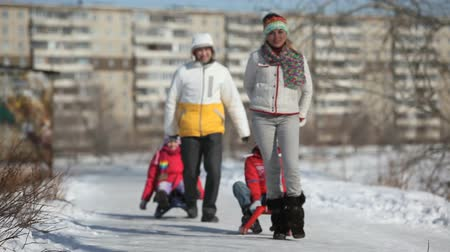 vago : Parents giving their children a sledge ride in urban surroundings Vídeos