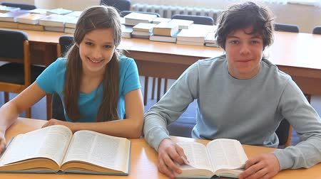 ler : Pupils reading textbooks then looking at camera which moves to the left