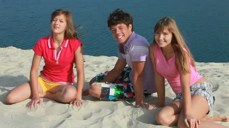 három ember : Three teenagers enjoying themselves at seashore and smiling at camera Stock mozgókép