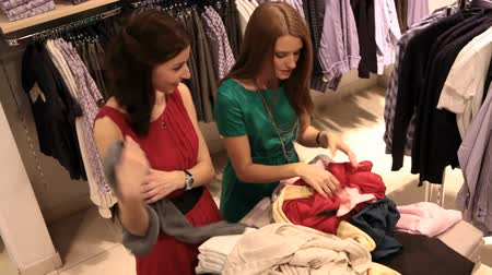 két : Young women looking for best pieces of clothes in the heap