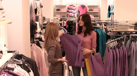pulóver : Happy friends doing shopping and choosing a sweater to try on