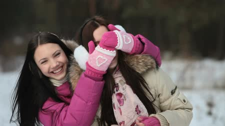 mittens : Girl covering her friend's eyes and asking if she can guess who Stock Footage