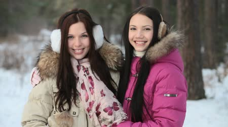 o : Two girls hugging and laughing in a wintry forest