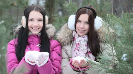 throwing in : Two girls simultaneously throwing snow in front of the camera
