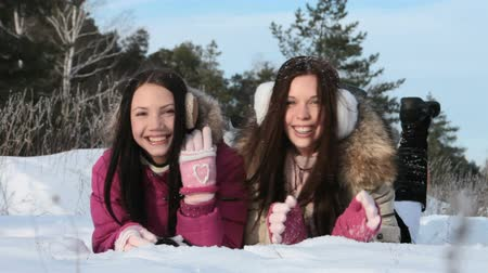 zmrazit : Two joyful girls lying in snow Dostupné videozáznamy