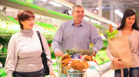 идущий : Family going through vegetable section, grandmother taking lettuce and little boy bringing pineapple Стоковые видеозаписи