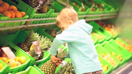 фрукты : Boy quickly taking a pineapple in supermarket and carrying it away