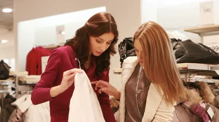 két : Two girls picking a white shirt in the shopping mall