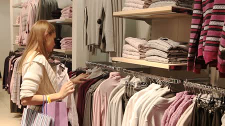 feltörés : Pretty blond girl choosing a blouse and a matching cardigan in mall