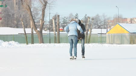 zmrazit : Dolly shot of couple skating on an open skating rink