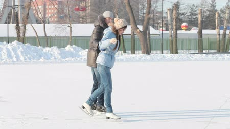 детеныш : Young people skating together on an outdoor ice rink, dolly shot