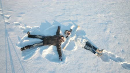 snow angel : Young couple lying on snow and making snow angels Stock Footage
