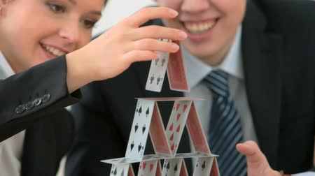 tricky : Two people in formal suits spending time building a house of cards