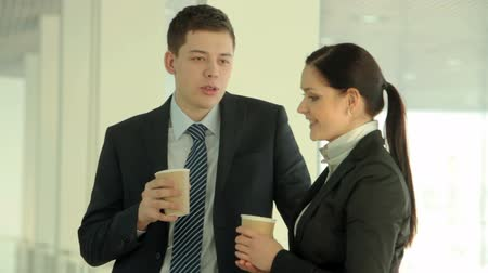 прихожая : Two businesspeople drinking coffee and talking during the break Стоковые видеозаписи