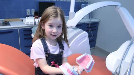 зубы : Little girl having fun in dentist's office playing with a jaw Стоковые видеозаписи