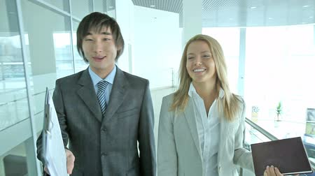 irodai dolgozó : Businessman with Asian appearance and his pretty colleague explaining business matters to the viewer, can be used in ads and commercials