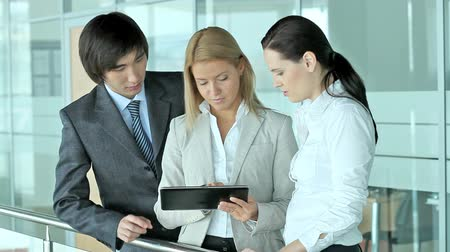 using tablet : Serious workers discussing business matters using modern technologies Stock Footage