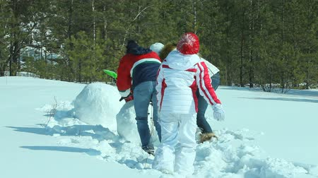 отдыха : Family making a snowman together, mom and daughters helping father to put one section on another
