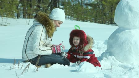kardan adam : Mom and daughter playing in snow, the snowman can be seen nearby Stok Video