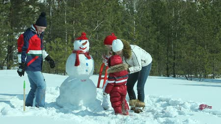kardan adam : Happy family of four painting the snowman made not far from winter forest