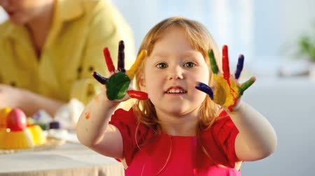 boldogság : Little girl with fingers and palms painted in multi colors looking cheerfully at camera and dancing Stock mozgókép