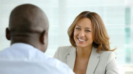 conversando : A pretty woman holding a job interview talking to an afro-american man