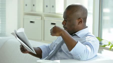 ler : Handsome African-American businessman reading newspaper on coffee break