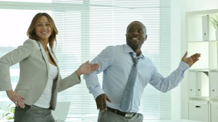 biznesmeni : Businesspeople dancing cheerfully in office in front of the camera