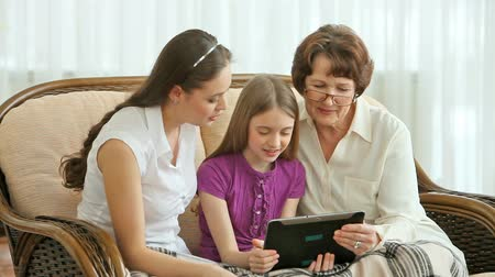 people talking : Women of three generations using modern technology to communicate