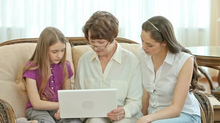 устройство : Grandchildren explaining their granny how to use a laptop Стоковые видеозаписи