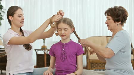 all ages : Two women of different age doing girl's hair, all three smiling