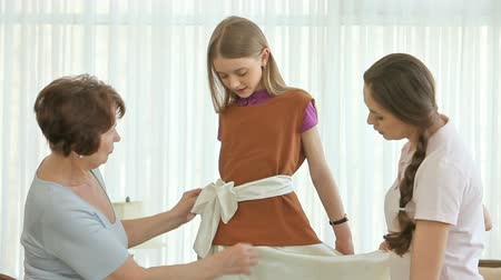 бабушка : Girl trying on a dress with a top and a silk belt, two women helping her
